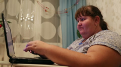 Overweight woman typing on computer at home Stock Footage