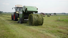 Tractor baler discharge round fresh hay bale during harvesting Stock Footage