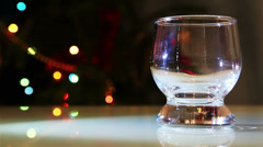 Whiskey with ice against festive lights background Stock Footage