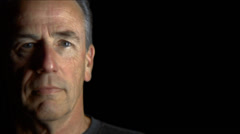 An older man looks to the camera calmly on a black background - stock footage