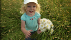 An adorable little girl waves, then shoves a bouquet of daisies into the lens. - stock footage
