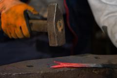 smith forging hot iron - stock photo