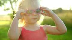 A cute little girl puts on a pair of diva sunglasses and plays with her hair - stock footage