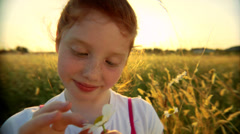 A cute redheaded young woman stands in a field and plays with some flowers - stock footage