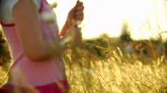 A cute redheaded girl stands in a field and plays with some flowers - stock footage