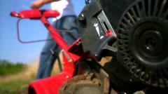 A man starting up a rotor tiller. Stock Footage