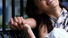 A young couple sit on a bench and hold hands and smile Stock Footage