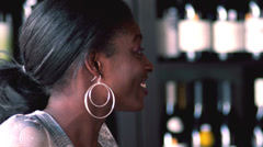 A young black couple sit at a bar and laugh and talk with each other - stock footage