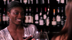 A young black woman talks to her friend at a bar Stock Footage