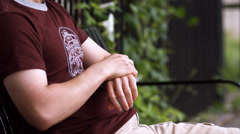A young adult male sits on a bench waiting and expressing sadness - stock footage