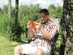 Man playing on tablet in the garden Stock Footage