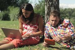 Pari työskentelee tabletin ja kannettavan puun alla varjossa Arkistovideo