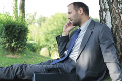 Businessman talking on the cellphone nd sitting on the grass Stock Footage
