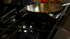 Vegetables in a skillet erupt in flame - stock footage