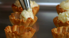 Freshly baked dessert cups get a tasty cream filling. Stock Footage
