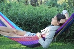 Businesswoman swinging in a hammock and drinking beer Stock Footage