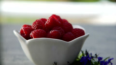 Whipped cream being put on top of a bowl of raspberries Stock Footage