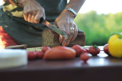 Woman's hands cutting bread with a knife Stock Footage