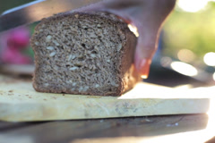 Woman's hands slicing bread with a knife Stock Footage