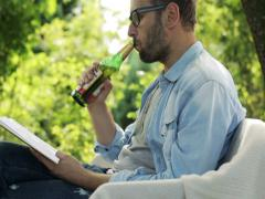 Man drinking beer and reading a book in the garden Stock Footage