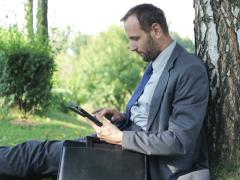 Businessman sitting under the tree shadow and working on his tablet Stock Footage