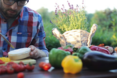 Man cutting blue cheese and sitting by the table in the garden Stock Footage