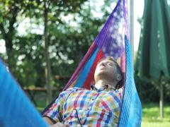 Man waking up in the hammock after the short nap Stock Footage