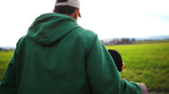 A father and son working on a farm, walk into the sunset - stock footage