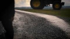 Viljelijä kävelee kohti traktorin varhain aamulla Arkistovideo