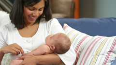 A newborn gets a slight tickle by his mother while she sleeps - stock footage