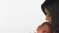 A mother holds her sleeping baby close to her chest Stock Footage