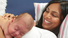 A newborn baby makes some funny faces while sleeping on top of her mother Stock Footage