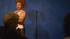 A young woman is up on stage giving a stand up comedy performance Stock Footage