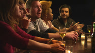 A group of friends make a toast at the bar and then take drinks Stock Footage