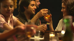 A group of friends spend time together drinking at a bar - stock footage