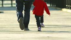 A little girl and her dad take a stroll down a boardwalk in New York City Stock Footage