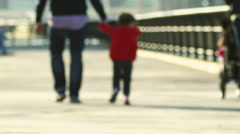 A little girl and her dad hold hands as they walk down a boardwalk together - stock footage