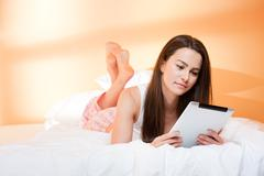 Beauty browsing.gorgeous young brunette woman using tablet computer in bed. Stock Photos
