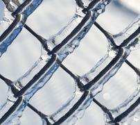ice coated chain link fence from an ice storm - stock photo