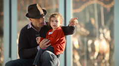 Father and daughter spend time together at a marry go round park - stock footage