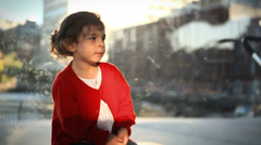 Little girl waits for the ferris wheel with anticipation - stock footage