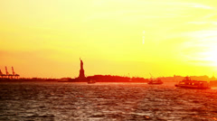 The sun sets over the Statue of Liberty, with boats going by in the water Stock Footage