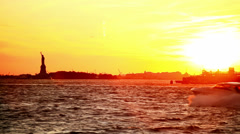 The sun is setting over the Statue of Liberty as a speed boat zooms by - stock footage