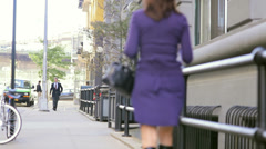 A man and a woman pass each other on the side walk while both on the phone Stock Footage