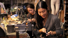Two friends sit and work together making crafts in a workshop Stock Footage