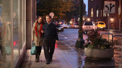 A couple walking down the street at night window shopping Stock Footage