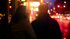 A couple walking away from the camera at night, with lots of city lights Stock Footage
