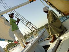 captain and a boy driving felucca boat - stock photo