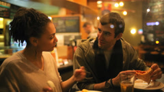 A cute young couple share a slice of pizza at the counter at night downtown Stock Footage