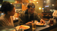 A good looking couple eat some pizza while on a date together - stock footage